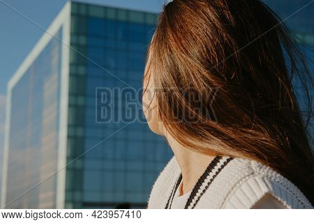 Back View Of A Woman With Long Hair Fluttering In Front Of The City Landscape