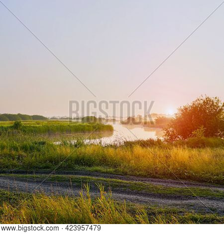Sunrise In A Light Fog On A Small River