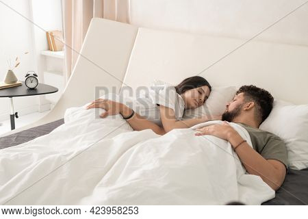 Amorous couple sleeping peacefully in bed in hotel room