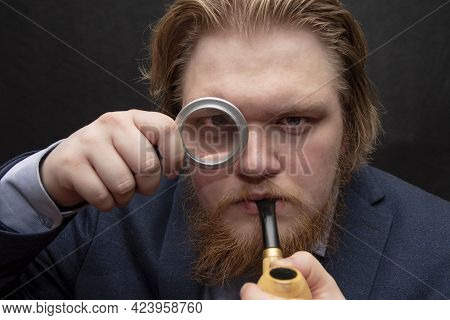 A 25-30-year-old Man Looks Through A Magnifying Glass And Holds A Pipe In His Hand, Close-up,selecti