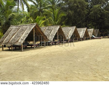 Thatched Bungalows With Sun Loungers On The Beach. Travel And Beach Concept