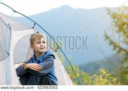 Hiker Child Boy Sitting Inside A Tent In Mountain Campsite Enjoying View Of Nature.