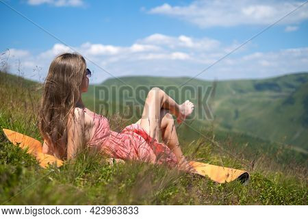 Young Woman In Red Dress Lying Down On Green Grassy Meadow On A Warm Sunny Day In Summer Mountains E