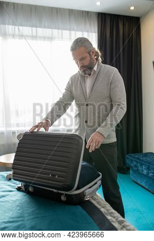 Mature male tourist opening suitcase while standing by bed