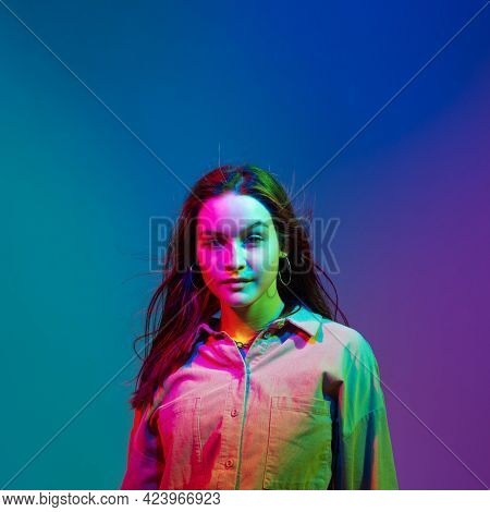 Confident Yong Stylish Modern Girl With Long Waving Hair Posing In Colourful Neon Studio Light. Woma