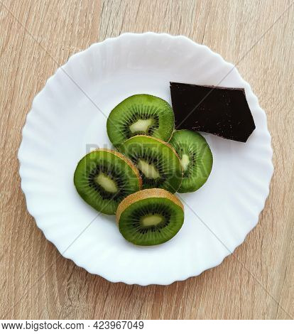A Few Pieces Of Kiwi And A Piece Of Dark Chocolate On A White Plate
