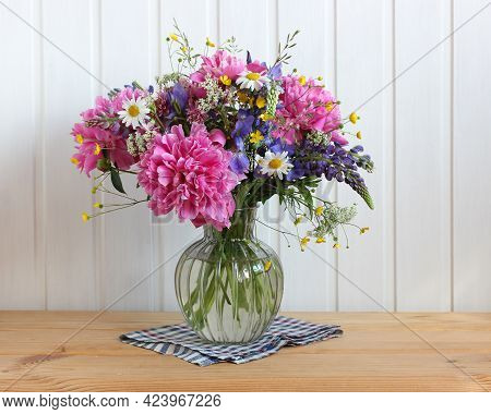 Garden And Wild Flowers And Herbs In A Glass Vase On The Table. A Bouquet Of Peonies, Daisies, Irise