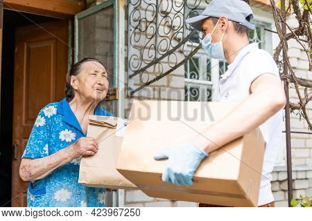 Young Male Volunteer In Mask Gives An Elderly Woman Boxes With Food Near Her House. The Son Helps A
