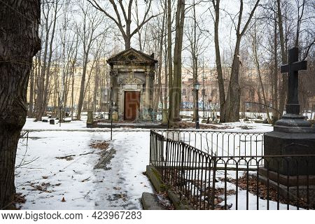 Crypt Of Horwitz Family, Large Stone Tomb Among Snow And Bare Trees In The Distance And Grave With B