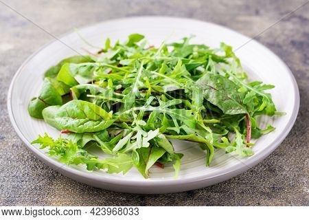 A Mixture Of Fresh Arugula, Chard And Mizun Leaves On A Plate  On The Table. Vegetarianism, Healthy