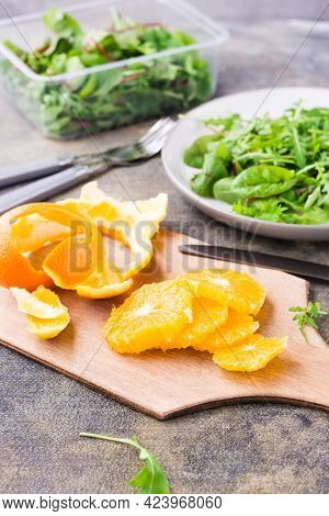 Peeled And Sliced Orange On A Cutting Board And A Mix Of Arugula, Chard And Mizun On A Plate On The