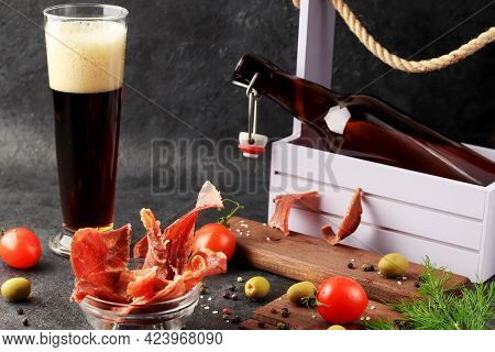 Pieces Of Jerky With Spices In A Glass Cup On A Dark Background. Condiments And Coarse Salt, Red Che