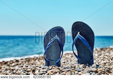 Blue Flip-flops On The Pebble Beach With Turquoise Sea And Blue Sky In Background. Summertime. Vacat