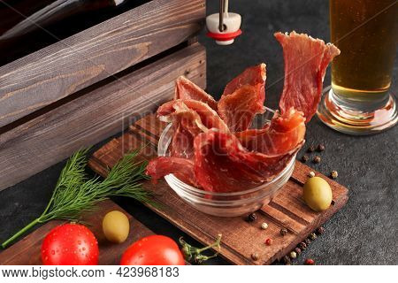 Pieces Of Spicy Jerky Meat In A Glass Cup On A Dark Background. Condiments And Coarse Salt, Red Cher