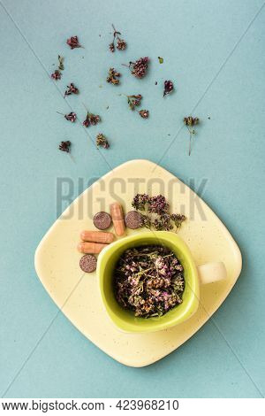 A Cup With Dried Oregano And Herbal Medicinal Capsules And Pills On A Saucer On A Green Background.