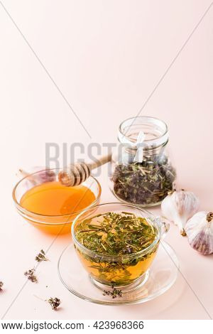 Hot Tea With Oregano In A Cup, Honey In A Bowl, Heads Of Garlic And Dry Herb In A Jar. Herbal Medici