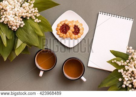 Two Mugs With Tea, Cookies, A Notebook And Bouquets Of Lilies Of The Valley On A Green Background. P