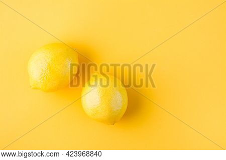 Two Ripe Whole Lemons On A Yellow Background. Detox Fruit Diet, Body Detoxification. Top View