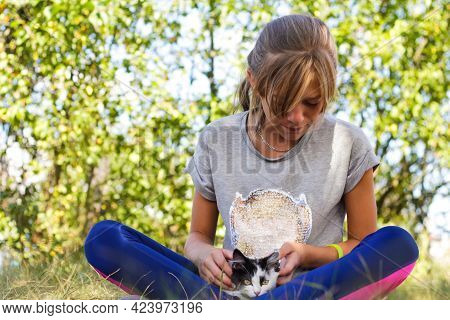 Defocus Blonde Little Girl Holding And Caress Cat, Black And White Small Crazy Kitten. Nature Green