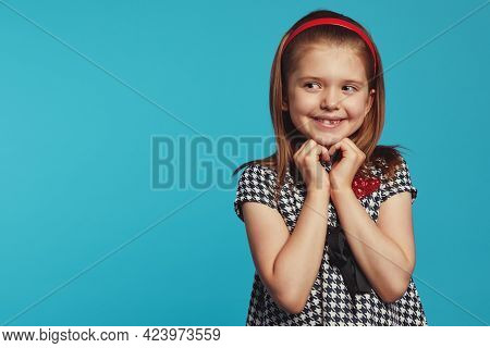 Delighted Girl Looking On Right Freespace, Smiling And Gesturing Heart