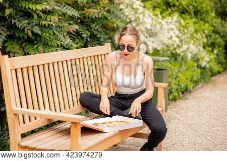 Young woman eating pizza in the park