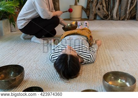 Singing Bowls Massage At Home: Two Women Practice Tibet Sound Therapy Together Using Vibrations And