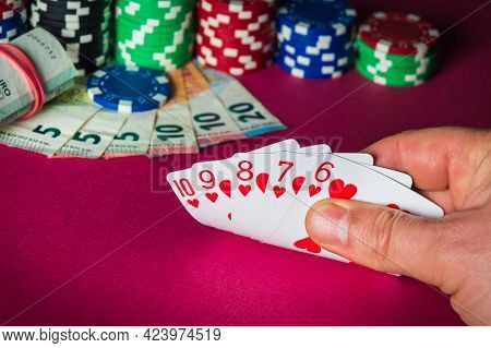 Poker Cards With Straight Flush Combination. Close Up Of Gambler Hand Takes Playing Cards In Casino.