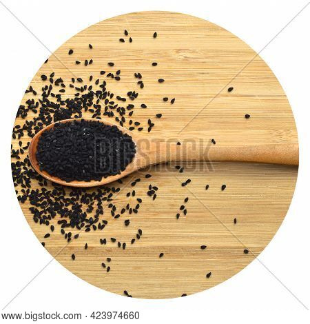 Many Dry Black Cumin In Wooden Spoon, On Bamboo Cutting Board