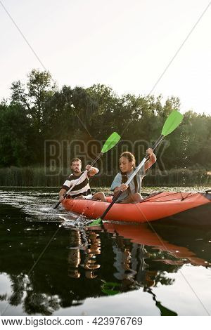 Concentrated Young Woman And Her Boyfriend Kayaking Together In A Lake On A Late Summer Afternoon. K