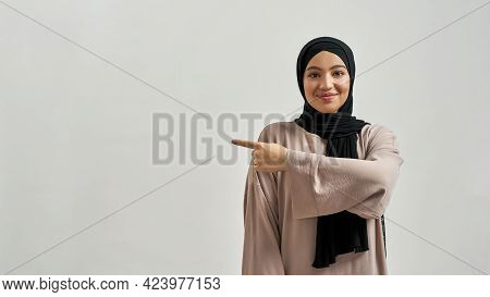 Happy Young Arabian Woman In Hijab Pointing To Side While Looking At Camera On Light Background With