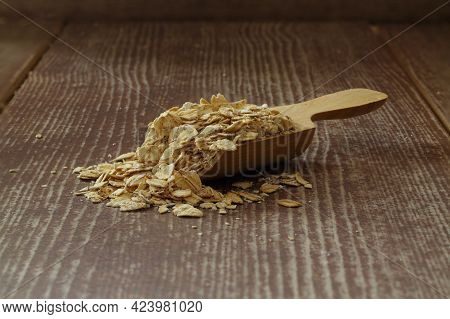 Oat Flakes In Wooden Spoon Isolated On Dark Background. Heap Of Oats For Package Of Oatmeal Or Grano