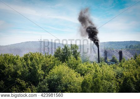 Smoke Plume From Industry Emitting Into The Atmosphere On Forest Trees Background And Blue Sky. Envi