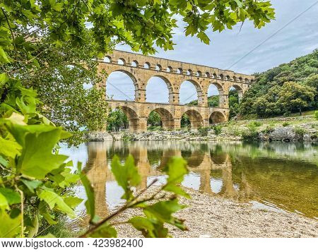 Roman aqueduct seen through foliage, Pont-du-Gard, Languedoc-Roussillon France