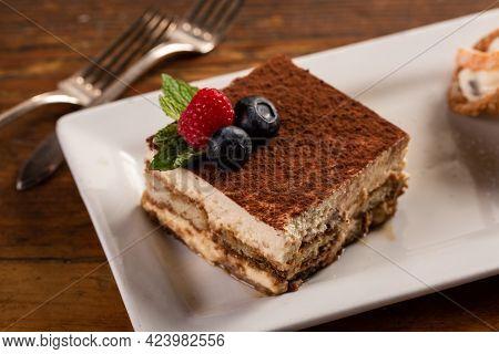Traditional Italian Desserts, Tiramisu And Cannoli On The Plate