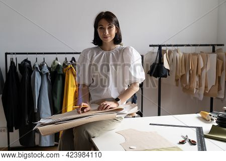 Portrait Of Young Woman Fashion Designer Sitting On Working Table In Clothing Studio Hold Paper Patt
