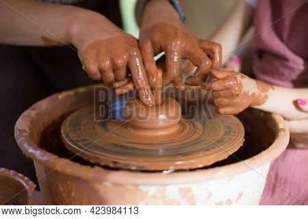 Master Class For The Child. Teacher Hands Show To Kid How Make Ceramics Dishes On Potter Wheel. Arti