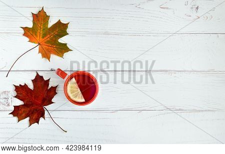 Light Wooden Background With Autumn Leaves Of Girlish Grapes, Ivy And A Cup Of Tea With Lemon. Autum