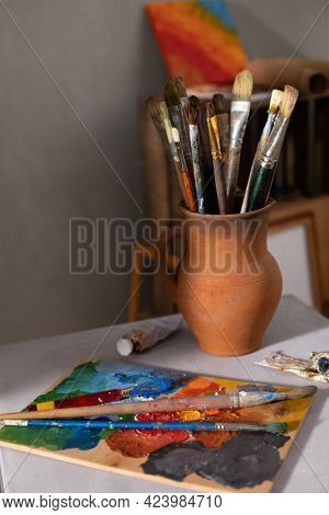 Paint brush in clay jug and palette at table. Art still life and paintbrush painting with painter tool