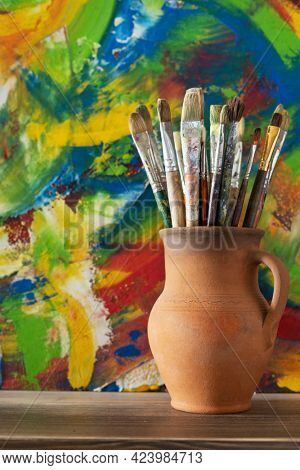 Paint brush in clay jug on wooden table background texture. Paintbrush  painting and art still life. Abstract art concept