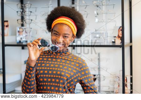 African Teen Girl Holding New Sunglasses Frames In An Optician Store.
