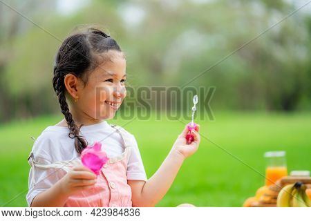 Happy Little Girl Blowing Soap Bubbles Playing Alone In The Park.