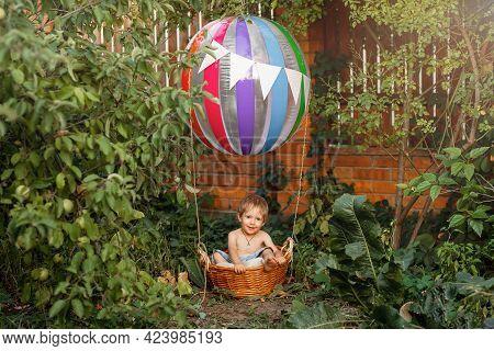 Pretty Child Riding Hot Air Balloon. Happy Kid Boy Having Fun Flying Up On Airship. Preschool Boy Tr