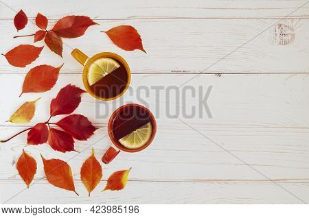 Light Wooden Background With Autumn Leaves Of Girlish Grapes, Ivy And Two Cups Of Tea With Lemon. Au