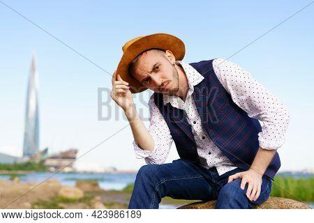 Close Up Portrait Of Handsome Stylish Casual Man Traveler In Hat Sitting At Sea Coastline And Enjoyi