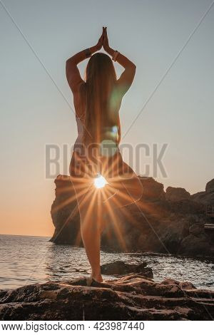 Young Woman With Long Hair In White Swimsuit And Boho Style Braclets Practicing Outdoors On Yoga Mat