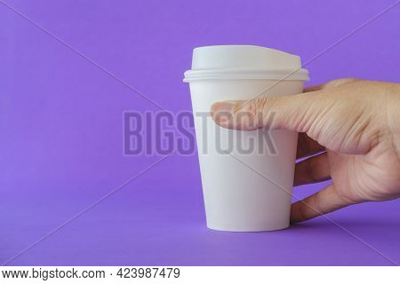 Close Up Of Man Hand Holding A White Paper Coffee Cup On A Purple Background.