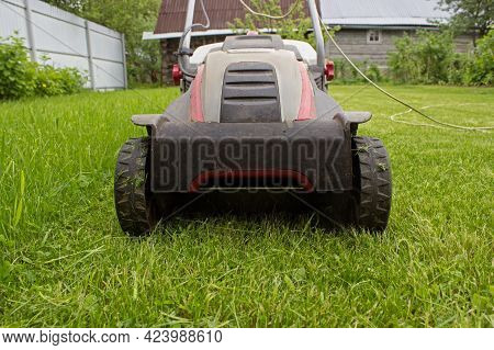 A Lawn Mower On A Lush Green. Gardening Background. Details Of Landscaping And Gardening