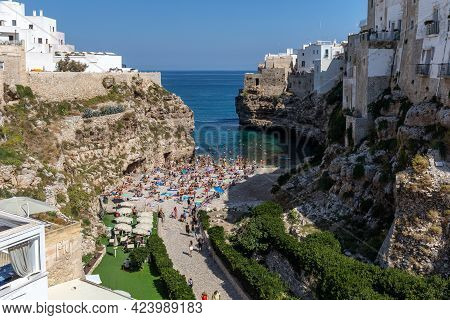 Polignano, Italy - September 17, 2019: People Relax And Swimming On Lovely Beach Lama Monachile In P