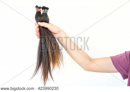 Cropped View Of Someone Hand Holding A Ponytail Cutting Hair For Donation. Usable Hair Can Turn Your