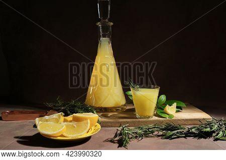 Limoncello Italian Alcohol Lemon Liqueur And Fresh Lemons On Dark Background.